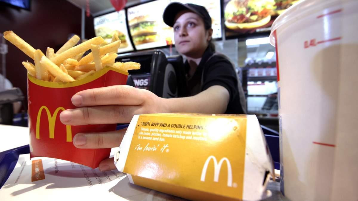 Работница McDonald's  выдает заказ